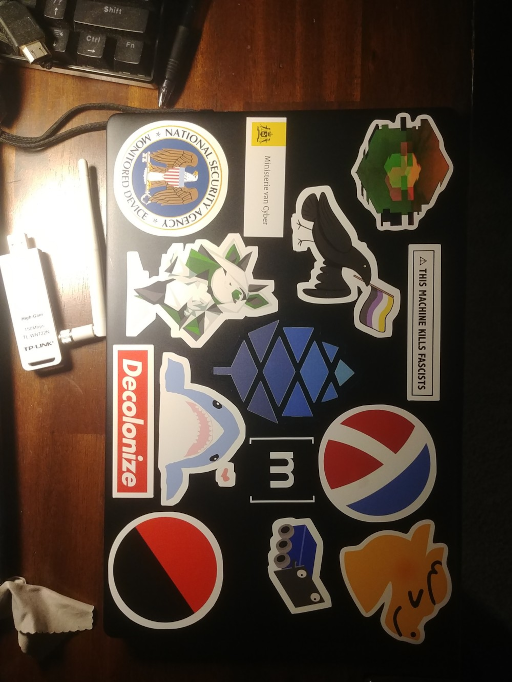 my pinebook pro on the desk with stickers: cybre, this machine kills fascists, racket, dragnpats, enby crow, matrix, FRC dozer, pine64, ministerie van cyber, nsa monitored device, libbie, blåhaj, decolonize, ancom circle